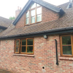 Exterior wood and brick work with brown stain, black stain on facia and sofits