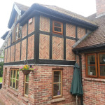 Exterior tudor style wood and brick work with black stain